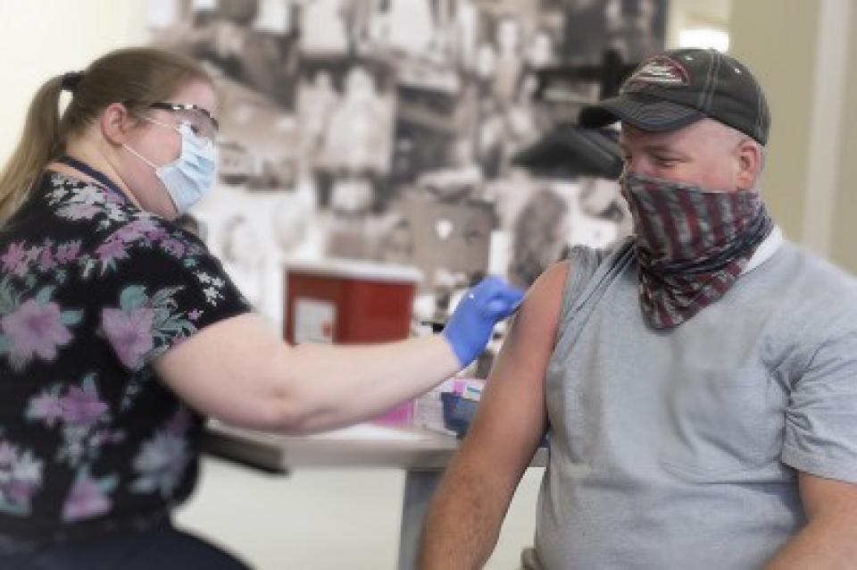 An EMT worker wearing a mask receiving his COVID vaccine in his right arm from a registered nurse